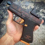 Glock G43x with custom Cerakote, laser engraving, and stippling, optic, threaded barrel. Custom Gun Shop.